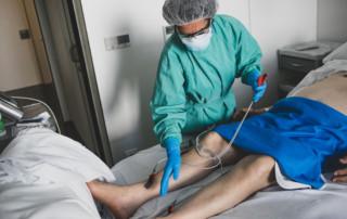 Infermera fent un electrocardiograma a un pacient hospitalitzat